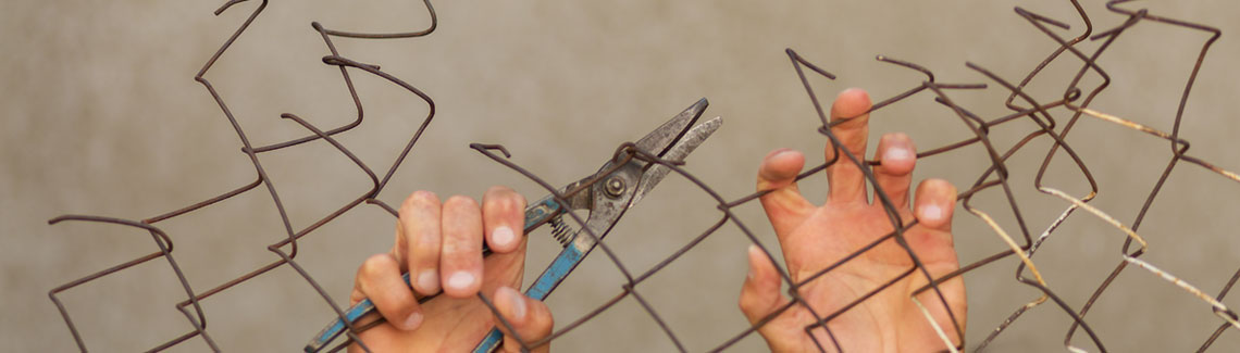 Refugees - Hands with clippers cut chain link fence.