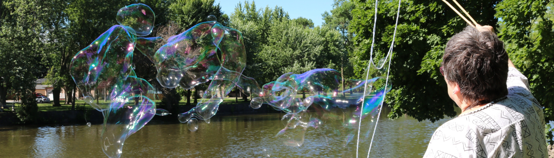 Harcourt congregant, Lynn Hancock, using two wands to blow big bubbles by the Speed River that flows through Guelph