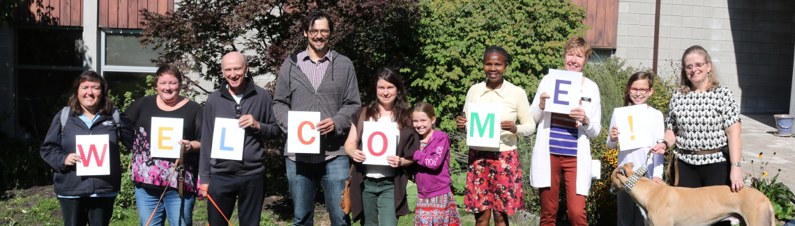 """People holding signs of each letter of the word """"WELCOME"""""""