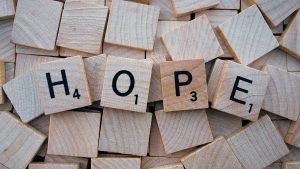 Scrabble letters that spell out HOPE.